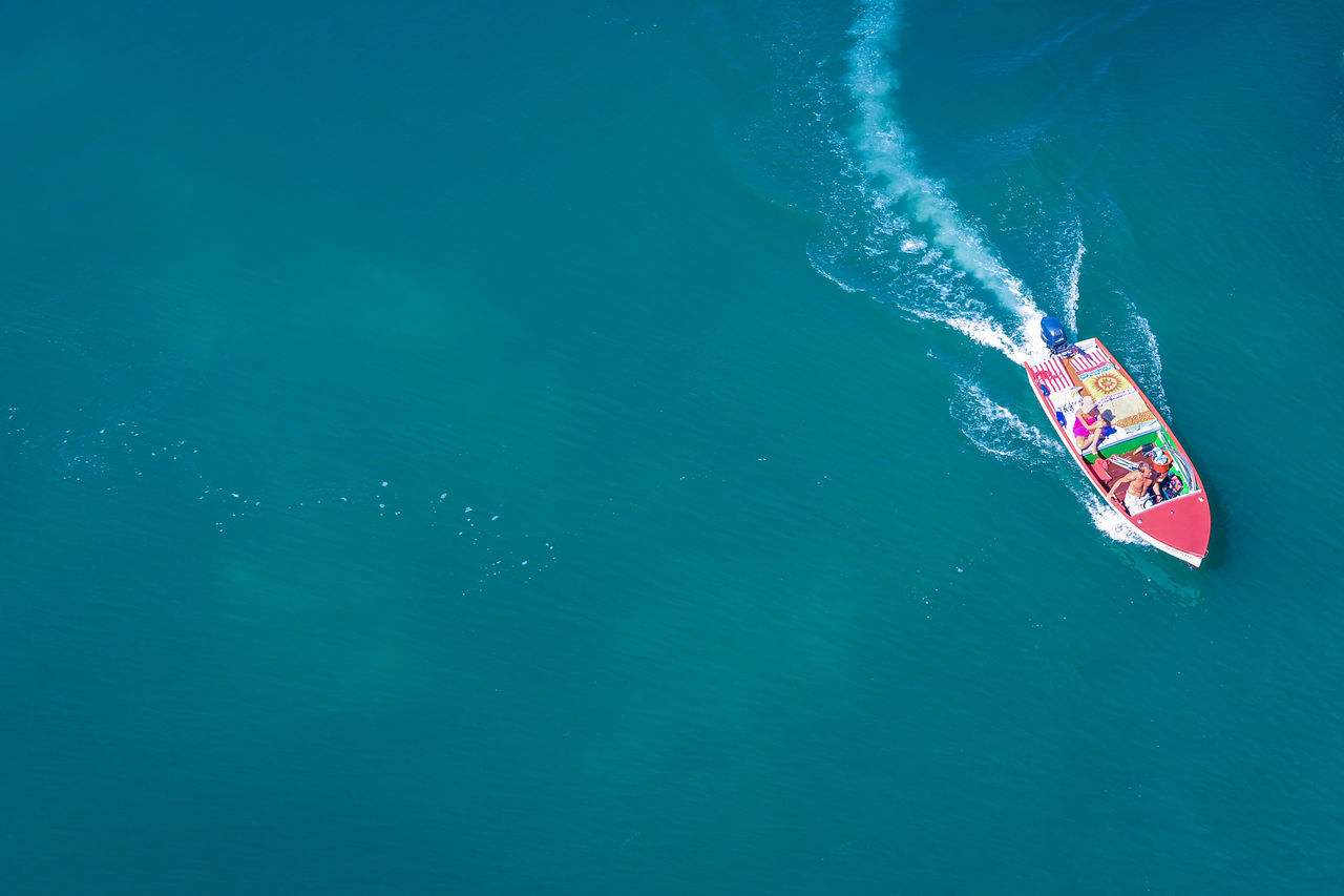 High angle view of people driving speedboat in ocean