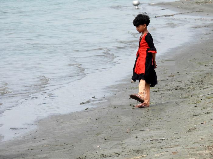 Side view of boy walking on beach
