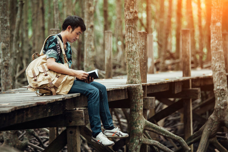Side view of young man holding book while sitting on footbridge in forest