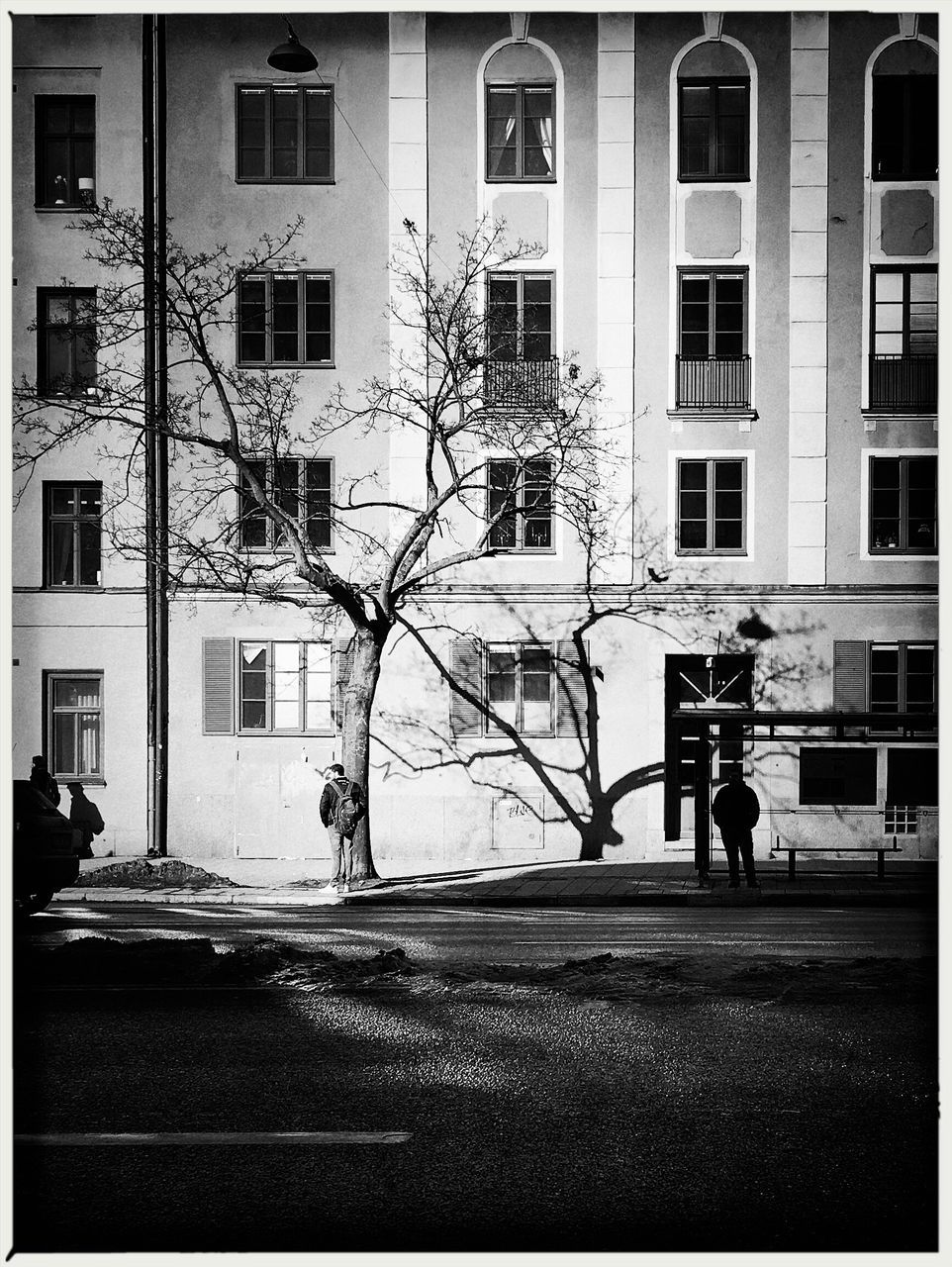 building exterior, architecture, built structure, street, city, outdoors, real people, city life, road, men, day, full length, one person, tree, people