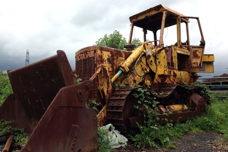 Abandoned earth mover on field
