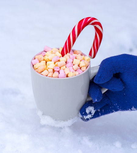 Cropped Hand Of Person Wearing Glove While Holding Marshmallows And Candy Cane In Cup During Winter
