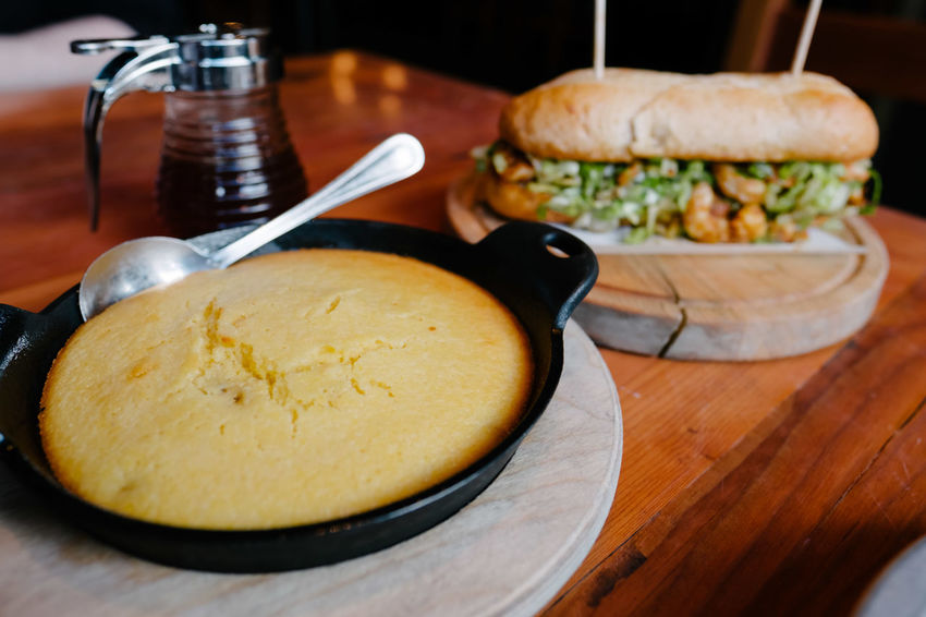 Skillet of cornbread with honey and a po'boy sandwich on a wood table. Food Table Day Restaurant Soul Food Food And Drink Sandwiches Indoors  Comfort Food Freshness Close-up No People Cast Iron Cornbread Poboy Ready-to-eat Southern Food Honey Temptation Indoors