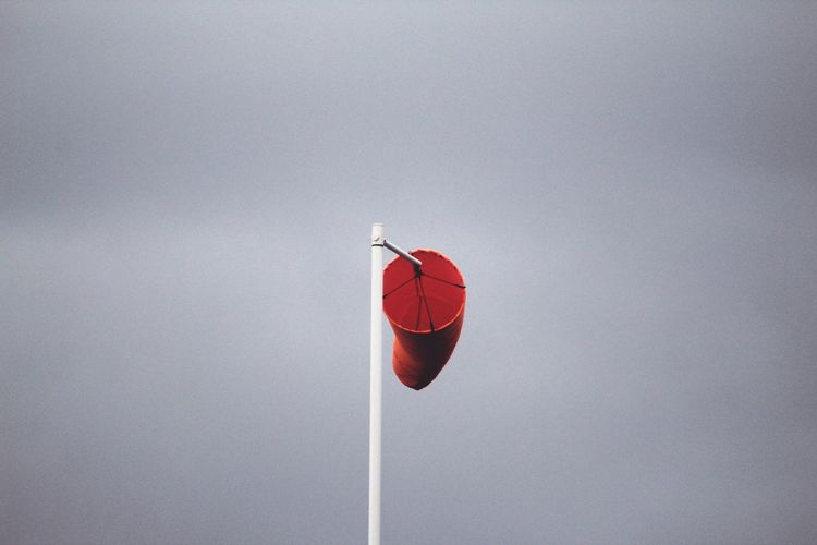 Low angle view of red wind sock against sky