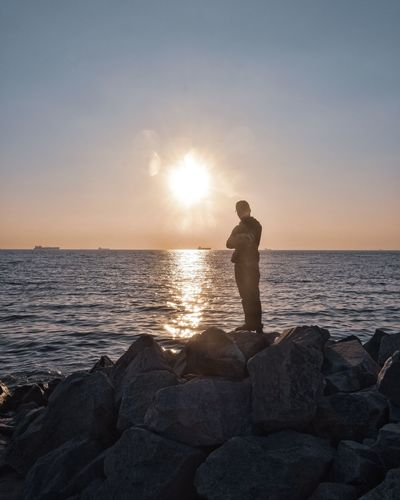 Man standing on rocks at sea shore against sky during sunset