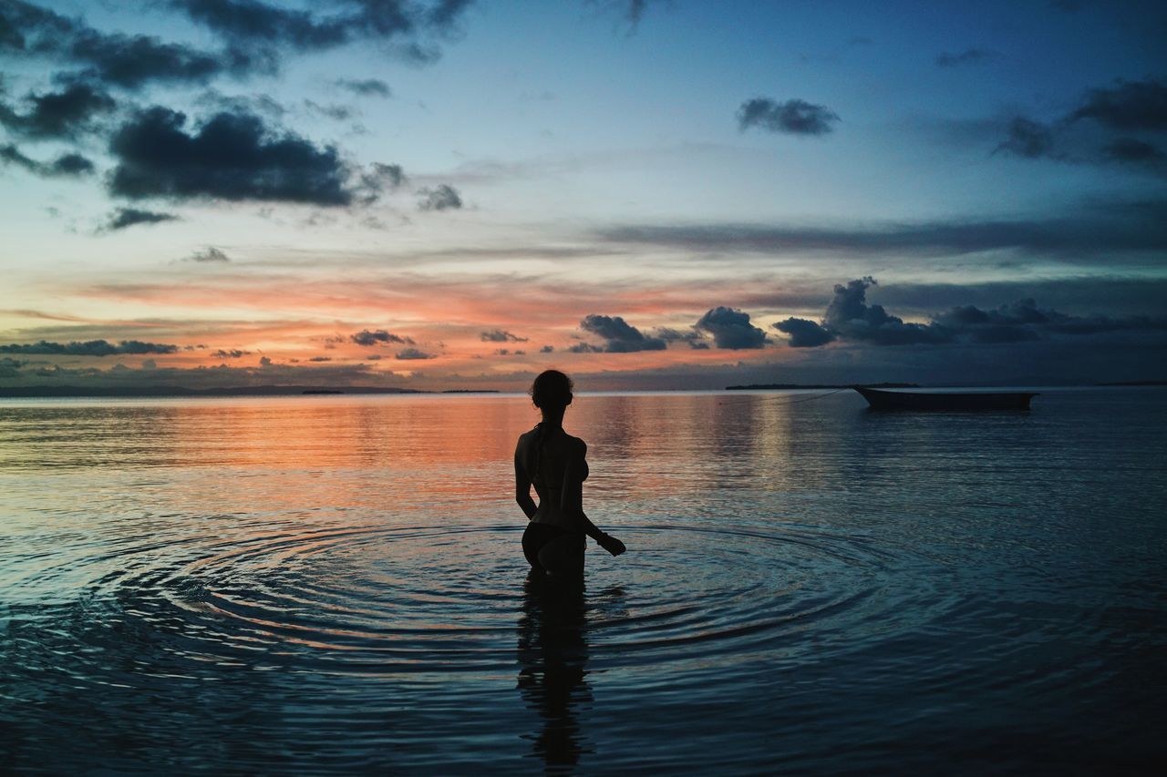 Rear View Of Woman Standing In Rippled Sea During Sunset