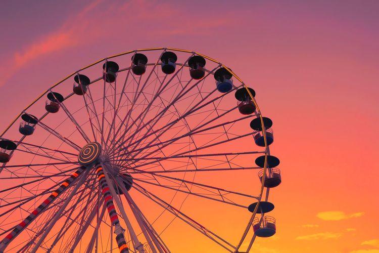 Low angle view of ferris wheel against orange sky