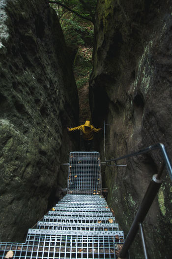 Hiker in yellow raincoat climbing up stairs amidst rocks