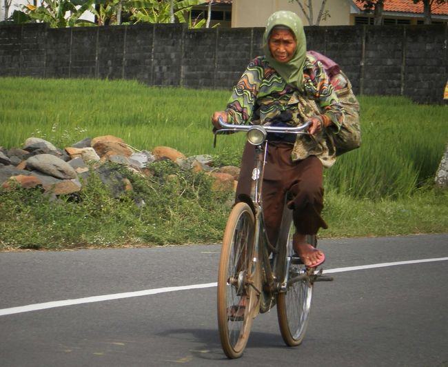 Senior Woman Riding Bicycle On Road