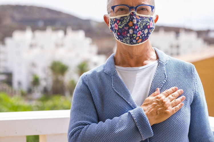 Midsection of senior woman wearing mask gesturing while standing outdoors