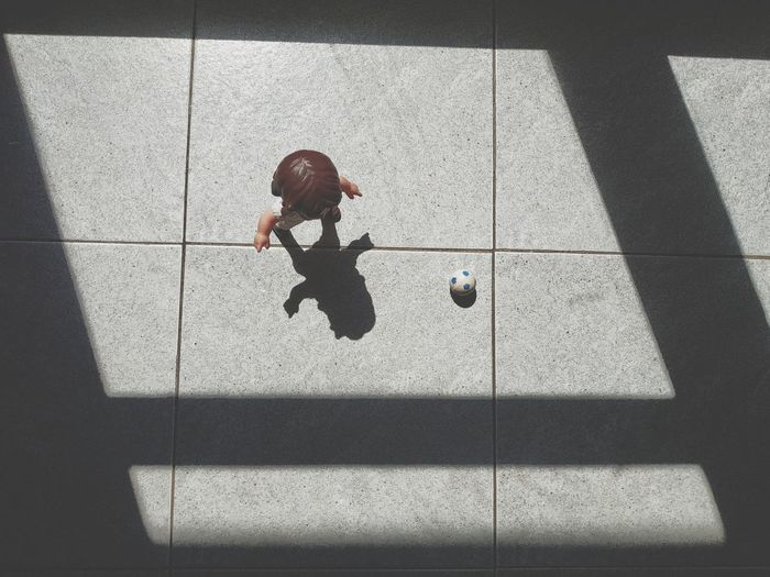 High Angle View Of Doll And Ball On Tiled Floor
