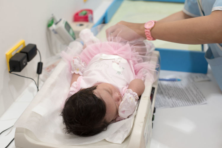 Close-up of baby lying on scales