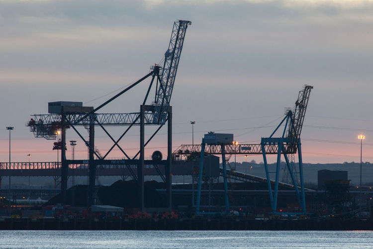 Cranes at commercial dock against cloudy sky at dusk