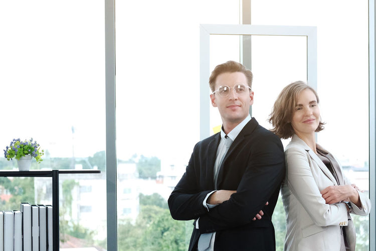 Portrait of a smiling young couple standing against window