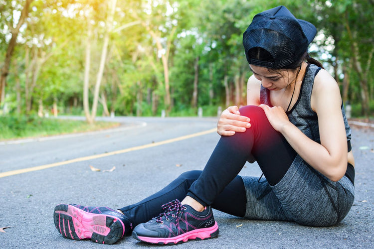 Woman Wearing Sports Clothing With Knee Pain Sitting On Road