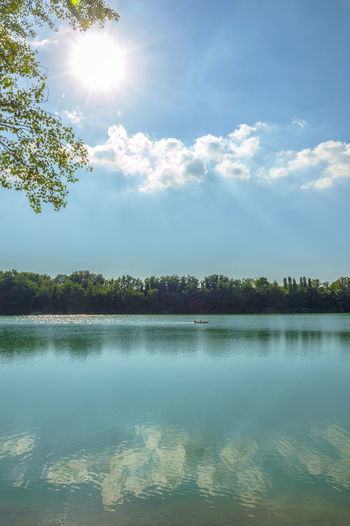 Forli, Italy, blue water lake with canoe in a sunny day Beauty In Nature Bright Cloud - Sky Day Lake Lens Flare Nature No People Non-urban Scene Outdoors Plant Reflection Scenics - Nature Sky Sun Sunbeam Sunlight Tranquil Scene Tranquility Tree Water