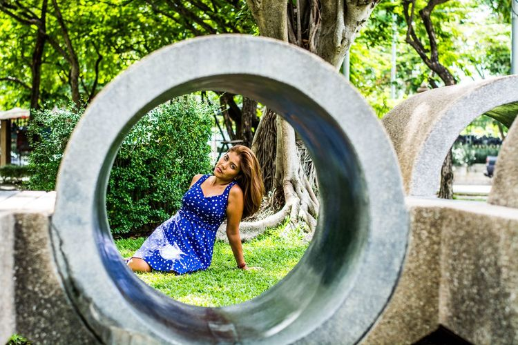 Portrait of woman sitting in park seen through wrought iron