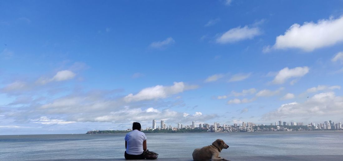 Rear view of woman with dog at sea against sky