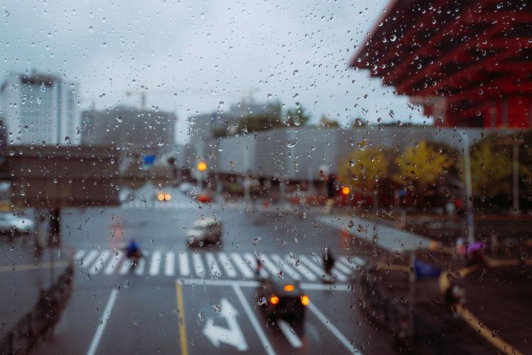 Cars on road seen through wet glass window in rainy season