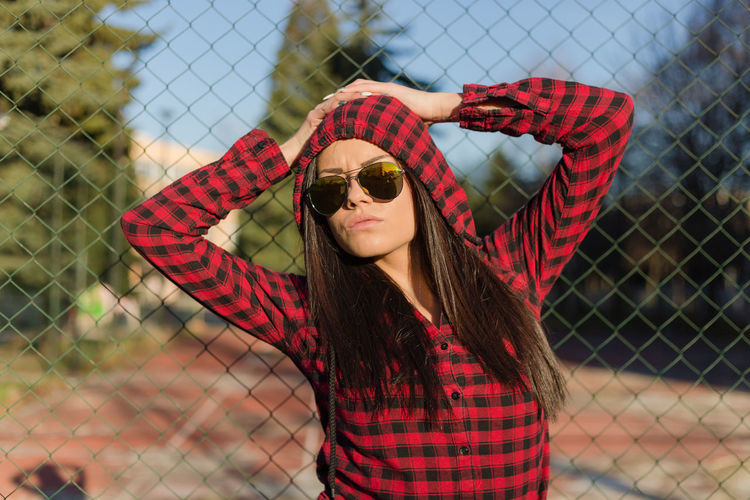Portrait Of Young Woman Wearing Sunglasses Against Fence