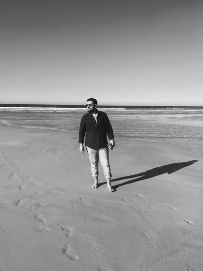 Full length of man standing at beach against clear sky
