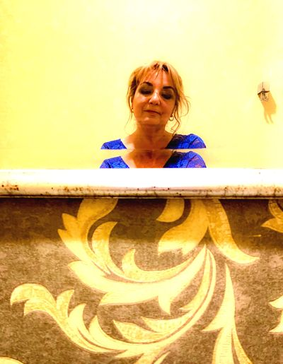 Portrait of a smiling young woman standing against yellow wall