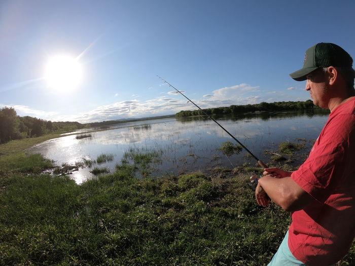Man fishing in lake against sky