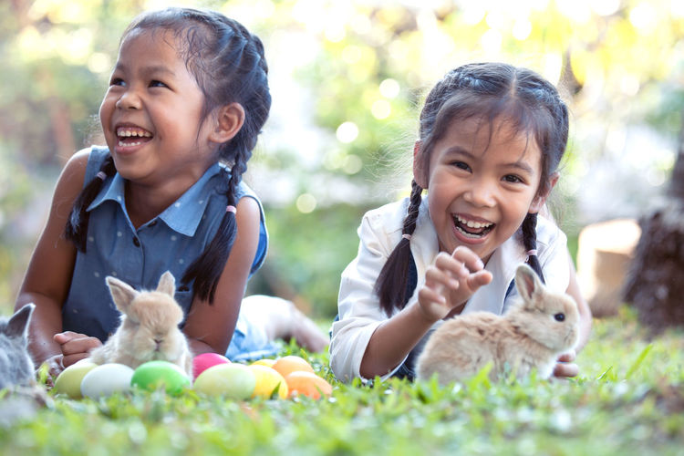 Smiling siblings with rabbits lying on grass
