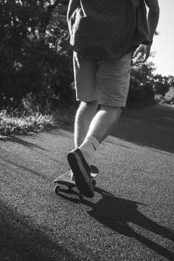 Low section of man skateboarding on road in city