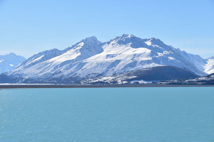 Scenic view of sea and snowcapped mountain against blue sky