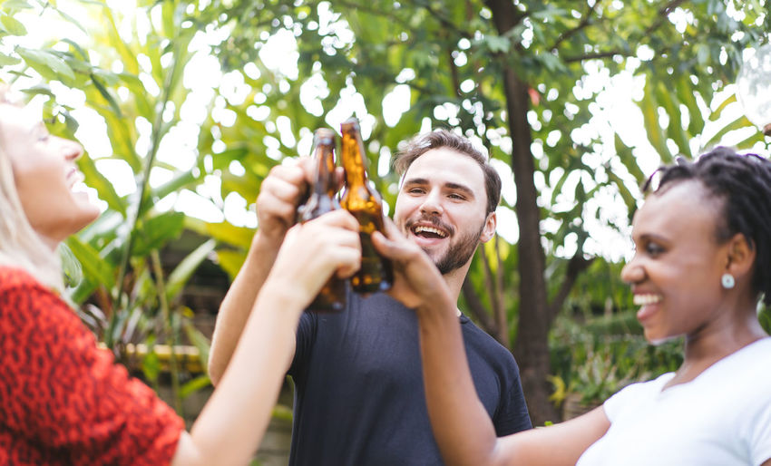 friends talking and toasting beers outdoors. Party people drinks toast celebration. Beer Beer - Alcohol Beer Glass Beers Drink Bottle Celebration Celebrating Celebrate BBQ BBQ Time Outdoors Park Garden Barbecue Barbecue Grill Grill Grilled Grilling African African Ethnicity Asian  Friendship Smiling Group Of People Happiness Women Headshot Holding Young Adult Enjoyment Togetherness Alcohol Celebratory Toast Young Women Adult Food And Drink Cheerful Refreshment Drinking Glass