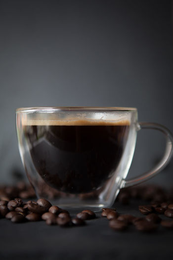 Coffee cup with fresh brewed coffee and brown roasted coffee beans scattered on black stone background side view Cup Food And Drink Drink Mug Refreshment Coffee Studio Shot Indoors  Coffee - Drink Roasted Coffee Bean Food Freshness Coffee Cup Close-up No People Hot Drink Table Transparent Still Life Roasted Glass Black Background Crockery Caffeine Tea Cup