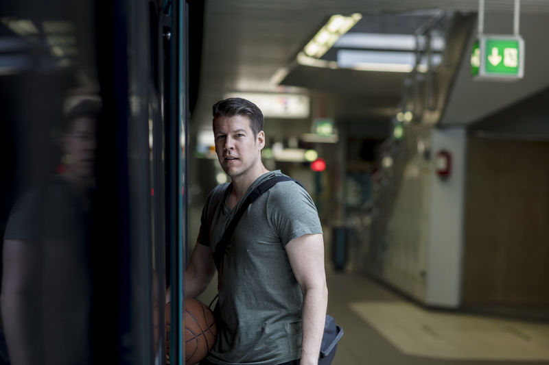 A fit male model with a basketball in hand enters a subway train. 1 Person Adult Athletic Basketball Entrance In Shape Man Metro Profile Public Transportation Stairs Bag Caucasian Fit Handsome Male Medium Shot Platform Shoulder Strap Subway Subway Station Train Train Station Urban V-neck