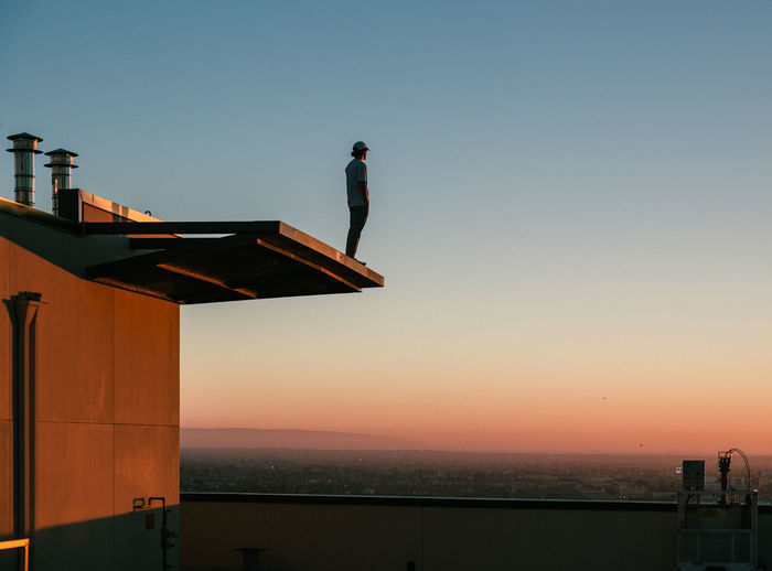 Man standing by sea against clear sky during sunset