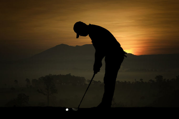 Silhouette Man Playing Golf On Field Against Sky During Sunset