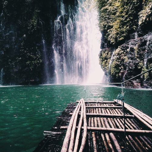 Wooden Raft In River Against Tinago Falls