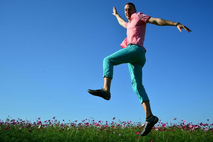 Portrait of happy man jumping over flowering field against clear blue sky