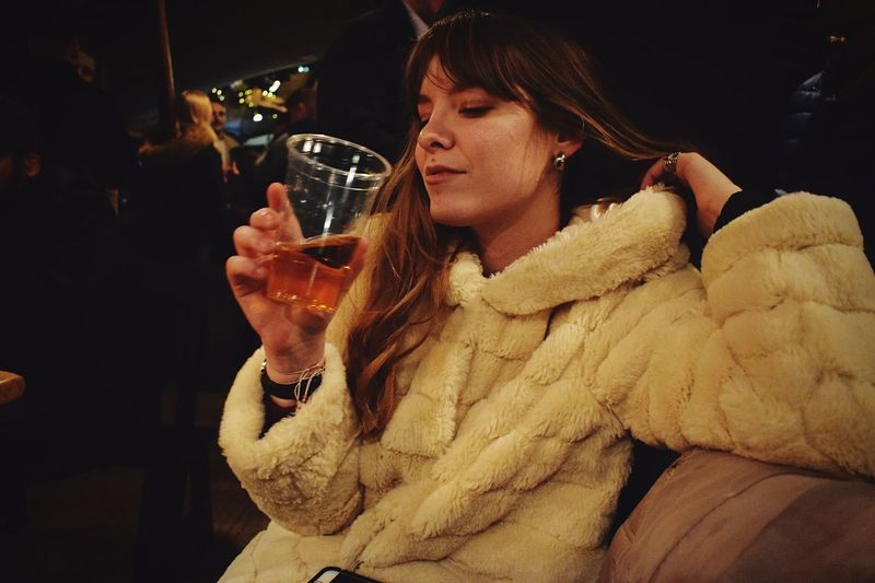Young woman wearing warm clothing having alcoholic drink at home