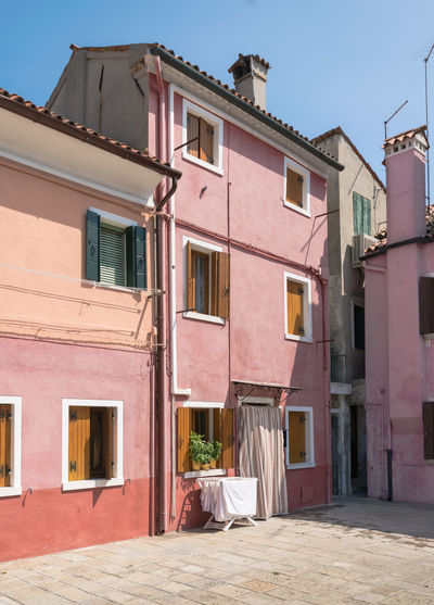 Typical Italian house painted in pink on a sunny summer day. Architecture Building Burano Burano Venice City Color Colorful Curtain Decor Decoration Design Detail Europe European  Exterior Façade Happiness Historical House Island Italy Lovely Mediterranean  Old Outdoor Outdoors Paint Pink Relax Rustic Street Summer Tourism Tourist Town Traditional Travel Venice Wall Window