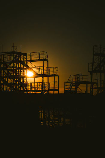 Sunset Sky Silhouette Nature Copy Space Architecture No People Built Structure Industry Outdoors Low Angle View Orange Color Construction Industry Night Illuminated Railing Staircase Construction Site Clear Sky Metal Construction Equipment