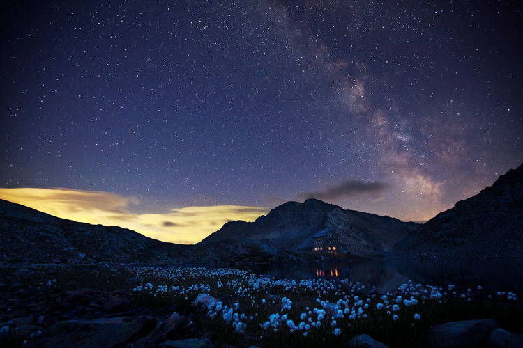 Scenic view of landscape and mountains against star field at night