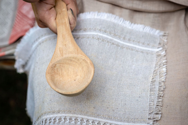 the woman makes traditional handcraft wooden spoon. - Image Craft Craftsman Craftsmanship  Craftsman Working Traditional Hand One Person Holding Human Hand Adult Human Body Part Kitchen Utensil Spoon Wood - Material Food And Drink Household Equipment Wooden Spoon Eating Utensil Occupation Close-up Preparation  Textile