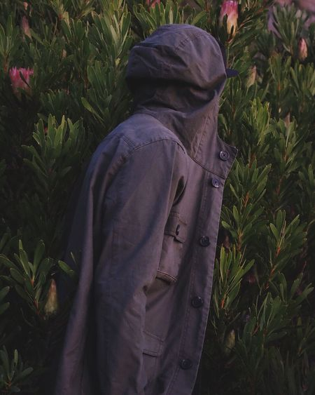 Side View Of Person In Jacket Standing By Plants