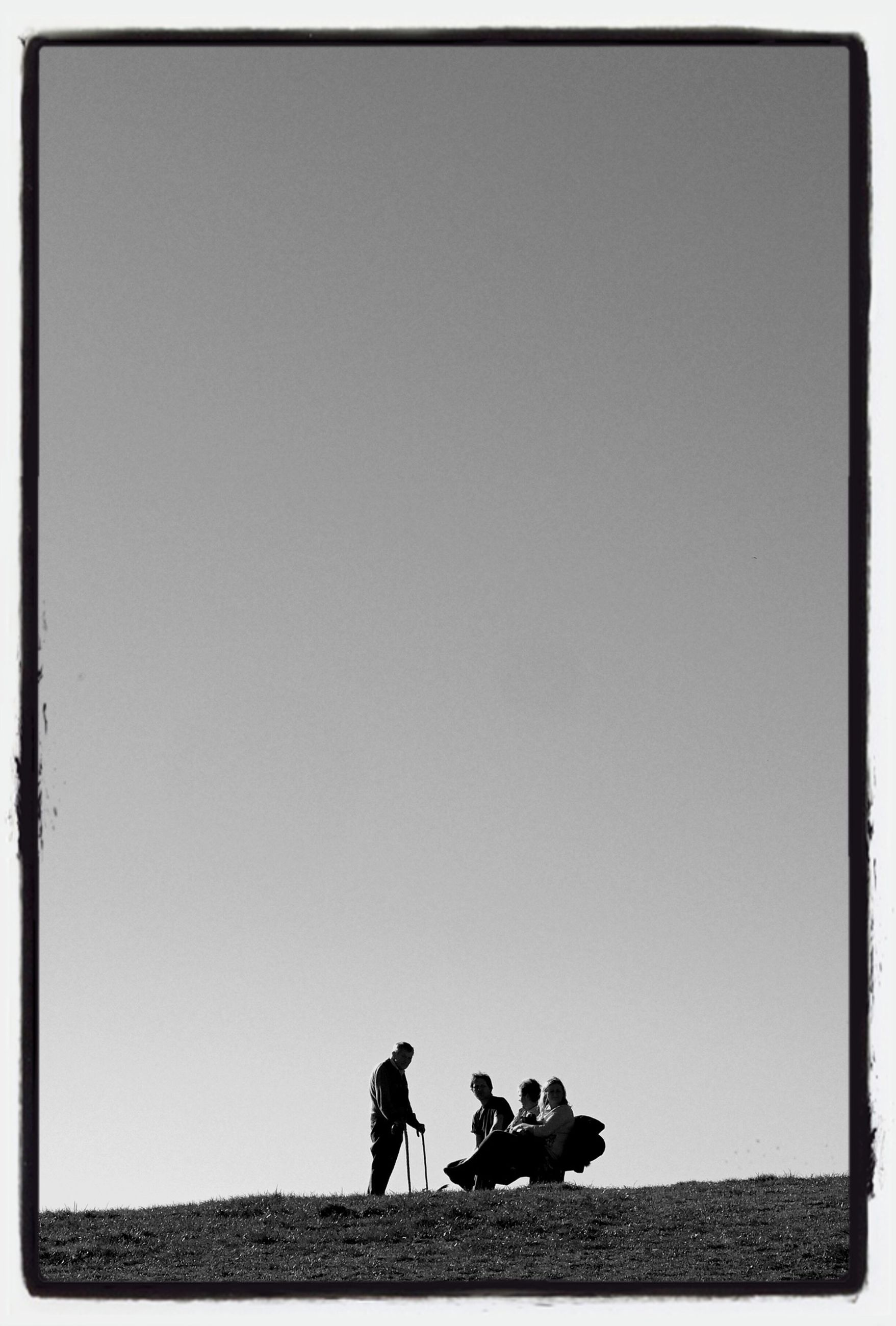 men, copy space, lifestyles, togetherness, leisure activity, clear sky, transfer print, silhouette, person, auto post production filter, bonding, rear view, sitting, full length, standing, friendship