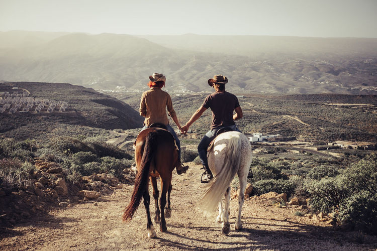 love and friendship concept outdoor for people ride horses in the countryside. amazing landscape and a world to discover traveling together Cowboy Love Animal Animal Themes Environment Friendship Full Length Horse Horseback Riding Landscape Livestock Mammal Mountain Mountain Range Nature Outdoors Pets Positive Emotion Real People Rear View Ride Riding Scenics - Nature Vertebrate Young Couple