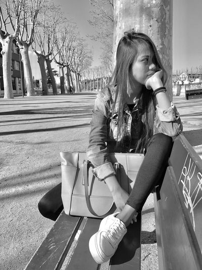 Thoughtful young woman sitting on bench at park