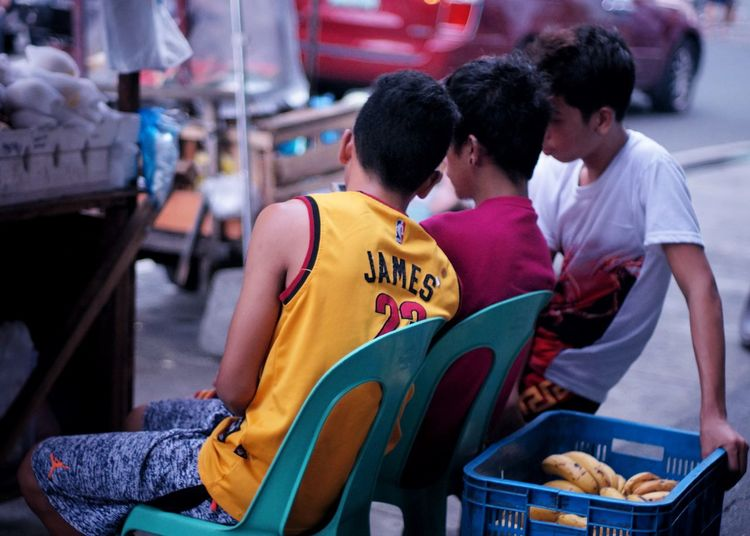 Smartphone Men ASIA The Week On Eyem Outdoors Selective Focus Market Street Photography Cubao Quezon City Philippines Street Vendor Real People Sitting Togetherness Friendship