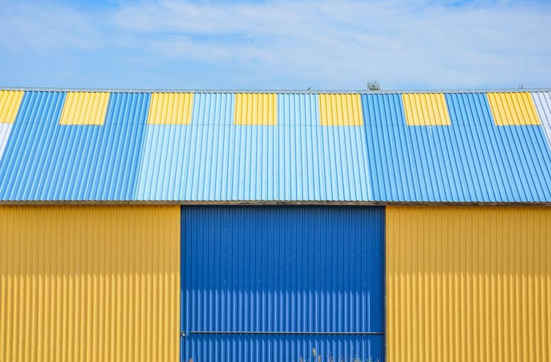 Low angle view of yellow and blue metal building against sky