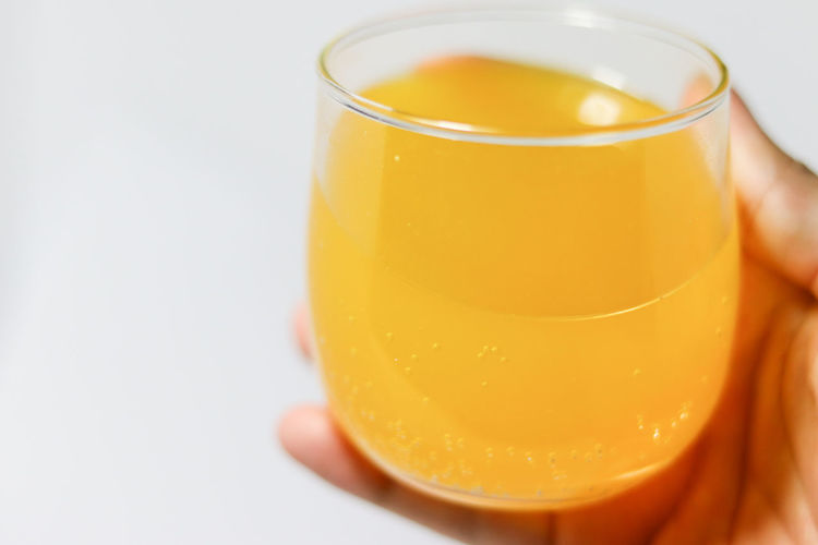 Close-up of hand holding drink against white background