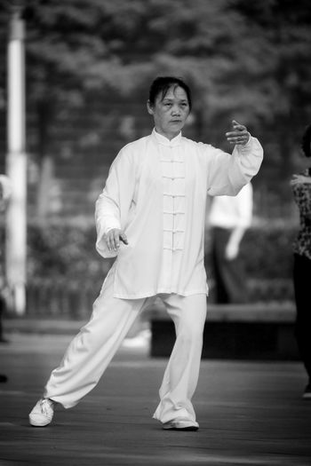 Woman practicig Tai Chi in public park in Shanghai Shanghai Tai Chi Chuan Woman China Court Day Exercising Focus On Foreground Front View Full Length Healthy Lifestyle Leisure Activity Lifestyles One Person Outdoors Park Real People Sports Clothing Standing Traditional